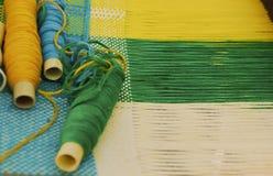 Tappninghandbok som väver vävstolen med oavslutat textilarbete fotografering för bildbyråer