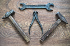 Tappninghjälpmedel (hammare, skiftnyckel, pojkar) på träbakgrund Arkivfoto