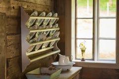 Tappninghylla med dekorativa plattor i gammal stuga Royaltyfri Foto
