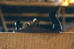 Tappninghyvlare på en träbrädenärbild med en rulle av shavings Arkivbild