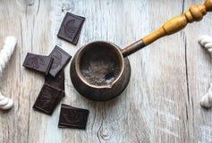 Tappningjezve med nytt bryggat kaffe Svart choklad med kakaobönaallsånger på trämagasinet med rephandtag turk royaltyfria foton