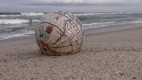 Tappningjordklot med den Amerika översikten på sand vid havet lager videofilmer