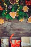 Tappningjulbakgrund med gran förgrena sig, dekoren för det nya året, ljust rödbrun kakor, kanderade frukter, kryddor och gåvaaska Arkivbilder