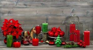 Tappningjulgarneringar med röda stearinljus och blommapoinse Arkivfoto
