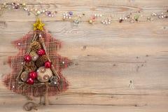 Tappningjulgran med säckvävbollar, kottar, träpinnar och röda äpplen på beige wood bakgrund Royaltyfri Foto