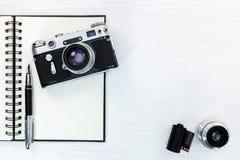 Tappningkamera, lins, filmrulle, öppen notepad med reservoarpennan Royaltyfri Foto