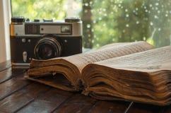 Tappningkamera och gammal bok på tabellen arkivbild