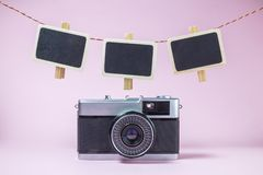Tappningkamera och tomma små svart tavlaklädnypor över på bakgrund för pastellfärgade rosa färger royaltyfri foto