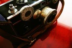 Tappningkamera på det körsbärsröda skrivbordet Arkivbilder