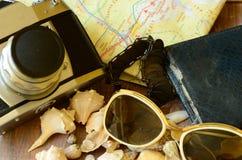 Tappningkamera, solglasögon, snäckskal, armband, översikt och plånbok Tappningresande Royaltyfri Fotografi