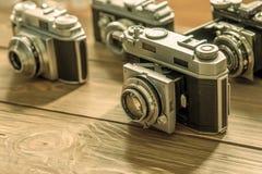 Tappningkameror och linser på träbakgrund royaltyfri bild
