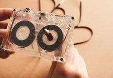 Tappningkassett och blyertspenna som spolar tillbaka bandet på brun bakgrund Royaltyfria Bilder