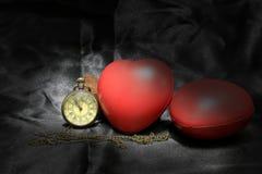 Tappningklocka och röd hjärta på svart bakgrund, förälskelse- och tidbegrepp i stillebenfotografi Fotografering för Bildbyråer