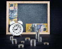 Tappningklocka, svart tavla, 50 australiska dollar räkning och mynt Arkivbild