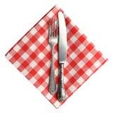 Tappningkniv och gaffel på röda den isolerade plädlinneservetten Royaltyfria Bilder