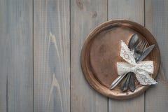 Tappningkniv, sked och gaffel på en metallplatta på en grå träbakgrund fotografering för bildbyråer