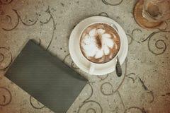 Tappningkopp kaffe och bok på tabellen Arkivbild