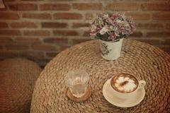 Tappningkopp kaffe och bok på tabellen Arkivfoto
