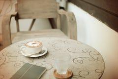 Tappningkopp kaffe och bok på tabellen Royaltyfria Bilder