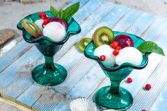 Tappningkoppar för grönt exponeringsglas med bollar för fruktglasssorbet tjänar som royaltyfri bild