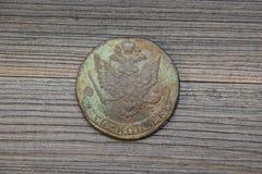 Tappningkopparryskt mynt med denhövdade örnen, 5 kopeks av Catherine The Great andra på en mörk träbakgrund Royaltyfri Foto