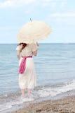 Tappningkvinna med slags solskyddanseende i vattnet på stranden Arkivbild