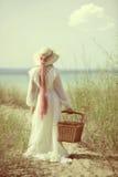 Tappningkvinna på stranden med picknickkorgen Arkivbild