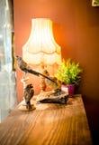 Tappninglampa och garneringobjekt på den wood tabellen Royaltyfri Bild