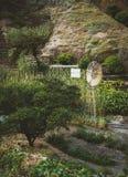 Tappninglantgårdväderkvarn bland frodig gräsplanträdgård Arkivbild