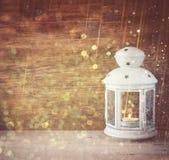 Tappninglyktan med bränningstearinljuset på trätabellen och blänker ljusbakgrund Filtrerad bild Royaltyfria Bilder