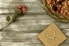 Tappningmagasin med kronblad av torkade rosa blommor, gåvaask som slås in i kraft papper på en grå tabell Plant utforma Kopiera u royaltyfri fotografi
