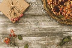 Tappningmagasin med kronblad av torkade rosa blommor, gåvaask som slås in i kraft papper på en grå tabell Plant utforma Kopiera u arkivbilder