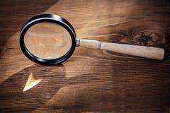 Tappningmagniferexponeringsglas på gammalt träbräde Royaltyfria Bilder