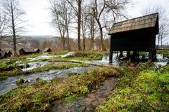 Tappningmaler trävatten ställningar på en snabb flödande flod i den forntida byn nära staden Jajce i Bosnien och Hercegovina Royaltyfri Foto