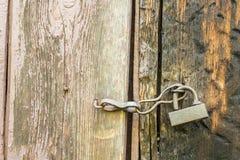 Tappningmetalllås som hänger på en gammal trädörr med skalning av PA Royaltyfri Fotografi