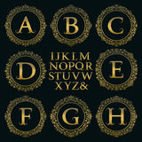 Tappningmonogramsats Guld- bokstäver och blom- runda ramar Arkivbild
