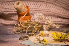 Tappningplats av gamla vykort, torkade blommor, antika exponeringsglas Arkivfoto