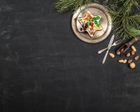Tappningplatta, sked och gaffel, muttrar, sötsaker och att sörja filialer på träsvart bakgrund royaltyfria bilder