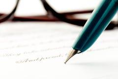 Tappningreservoarpenna som bakom skrivar ett brev, exponeringsglas royaltyfria bilder