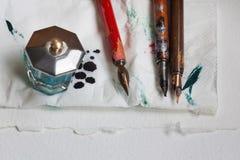 Tappningreservoarpennor med bläckhornjournalservetten Vitbok texturerad bakgrund Konstnärseminariumbegrepp Närbild Royaltyfri Foto
