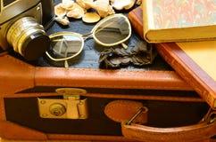 Tappningresväska, kamera, solglasögon, snäckskal, armband och en hög av böcker Tappningresande Royaltyfria Foton