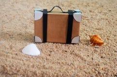 Tappningresväska på stranden arkivfoto