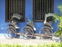 TappningRickshaw förutom den blåa herrgården som lokaliseras i Georgetown, Malaysia Arkivfoto