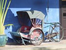 TappningRickshaw som för många år sedan används av kinesen för att transportera folk runt om stad Royaltyfri Foto