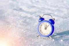 Tappningringklocka på snön på solnedgången Begreppet av jul och det nya året Arkivbild