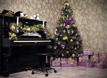 Tappningrum med ett piano, en julgran, stearinljus, gåvor eller en pr Royaltyfri Bild