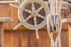 Tappningsegelbåtdäck med det gamla träroderhjulet och det nautiska blocket med rep royaltyfri foto