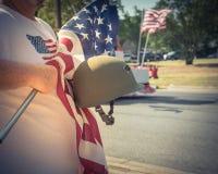Tappningsignalveteran med USA-flaggan och WWI-hjälmen ståtar på Arkivfoto