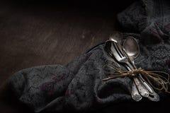 Tappningsilverskedar, gafflar och kniv på svart bakgrund för tappning Låg-tangent royaltyfri fotografi