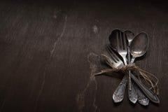 Tappningsilverskedar, gafflar och kniv på svart bakgrund för tappning Låg-tangent arkivbilder
